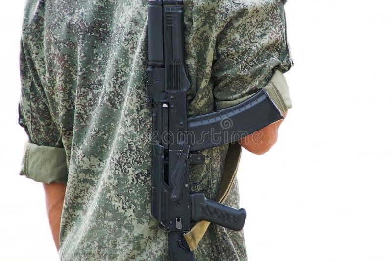 Ein Junge mit einem Gewehr in der Schutzkleidung kakifarbig auf einem weißen Hintergrund r?ckseite Patrouille oder Sicherheit Bun lizenzfreies stockfoto