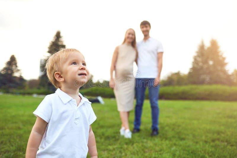 Ein Junge mit einem Spielzeug auf dem Hintergrund von Eltern im Park stockfoto