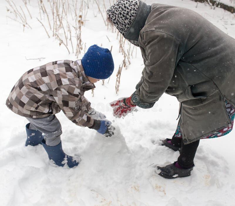 Ein Junge mit seiner Großmutter, die im Schnee spielt stockfoto