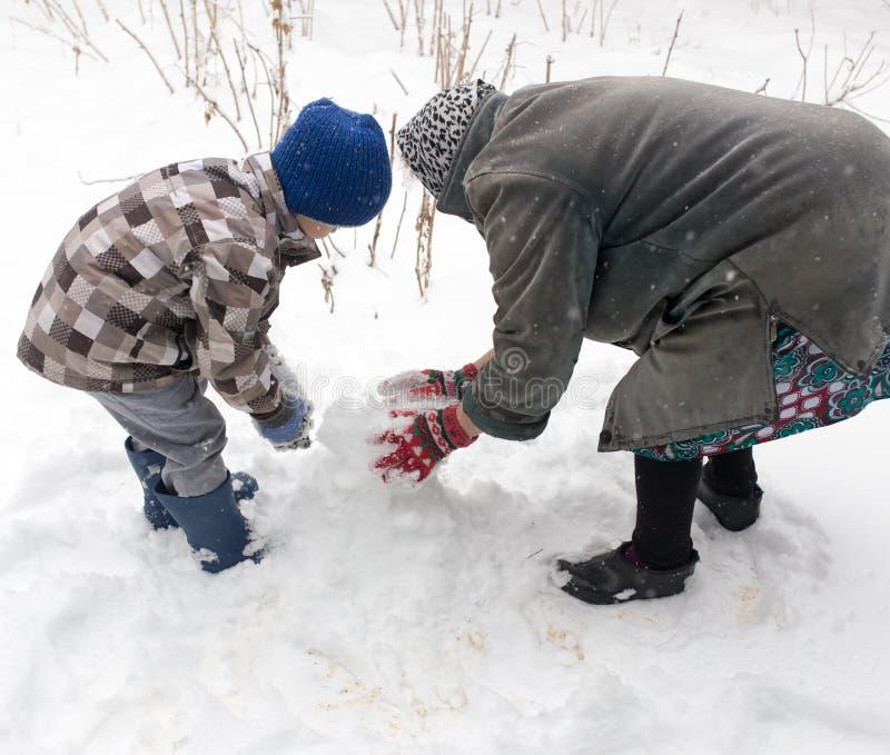Ein Junge mit seiner Großmutter, die im Schnee spielt stockbild