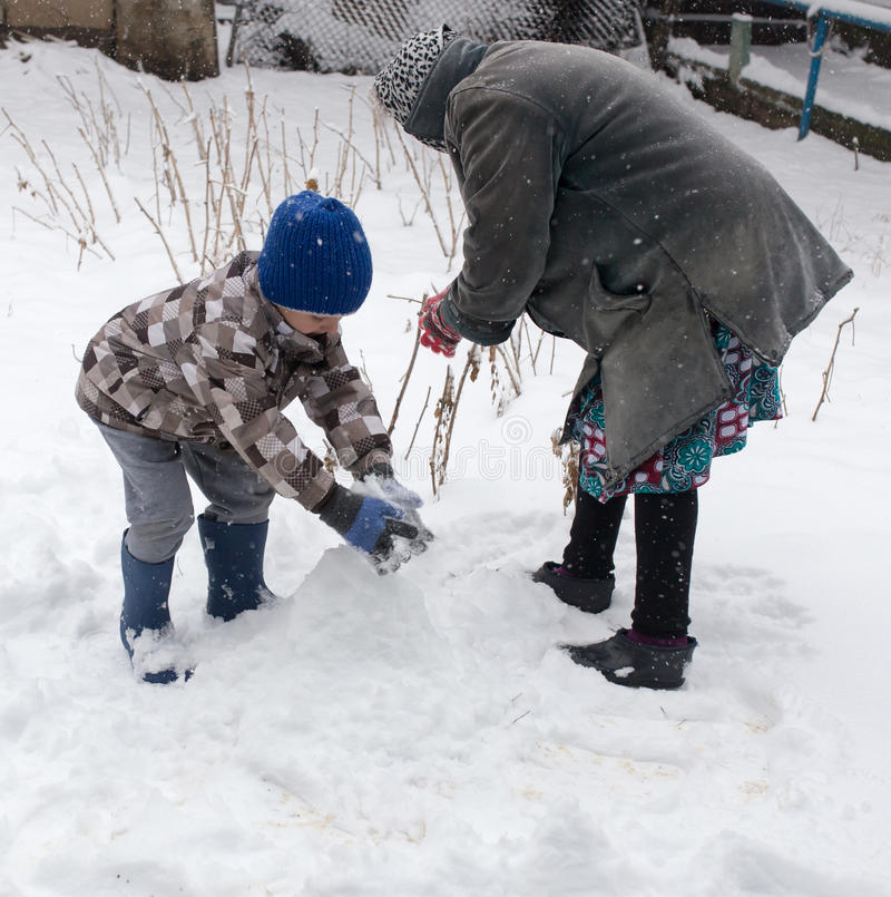 Ein Junge mit seiner Großmutter, die im Schnee spielt lizenzfreie stockfotos