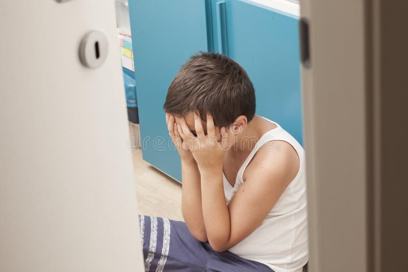Ein Junge setzt allein stockbilder