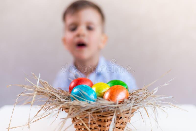 Ein Junge sieht mit Interesse und Neugier auf einen Korb mit mehrfarbigen Ostereiern auf einem Tisch auf weißem Hintergrund lizenzfreies stockbild