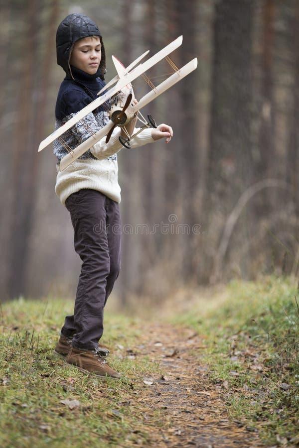 Ein Junge spielt im Wald mit einer Spielzeugfläche Herbstspiele im w lizenzfreie stockfotografie