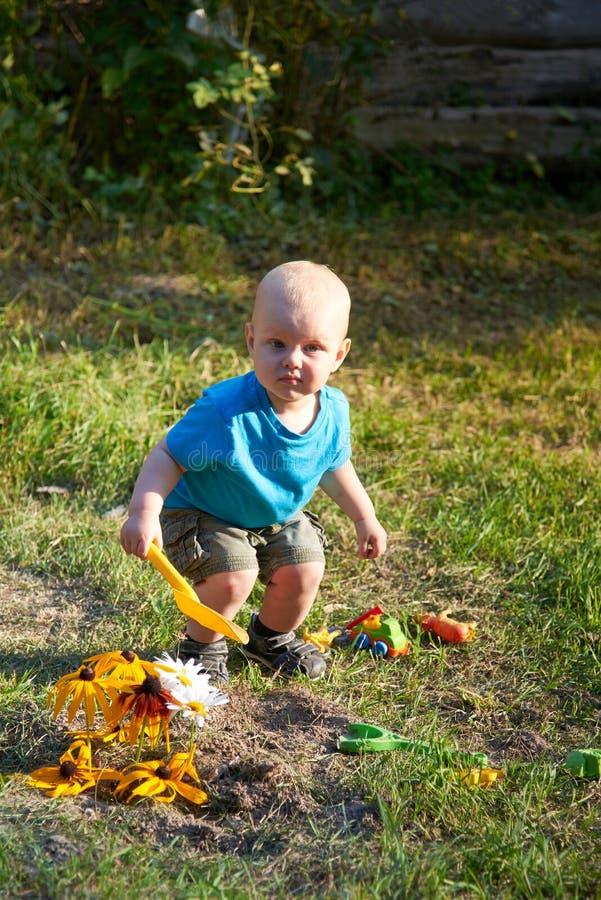 Ein Junge spielt mit Spielwaren auf dem Gras an einem warmen Sommertag stockfoto