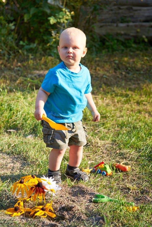 Ein Junge spielt mit Spielwaren auf dem Gras an einem warmen Sommertag stockbild