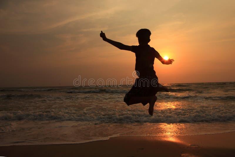 Ein Junge springt in die Wellen während des Sonnenuntergangs stockfoto