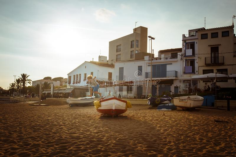 Ein Junge springt von einem Boot zum Sand in der Stadt von Blanes in Spanien lizenzfreie stockfotos