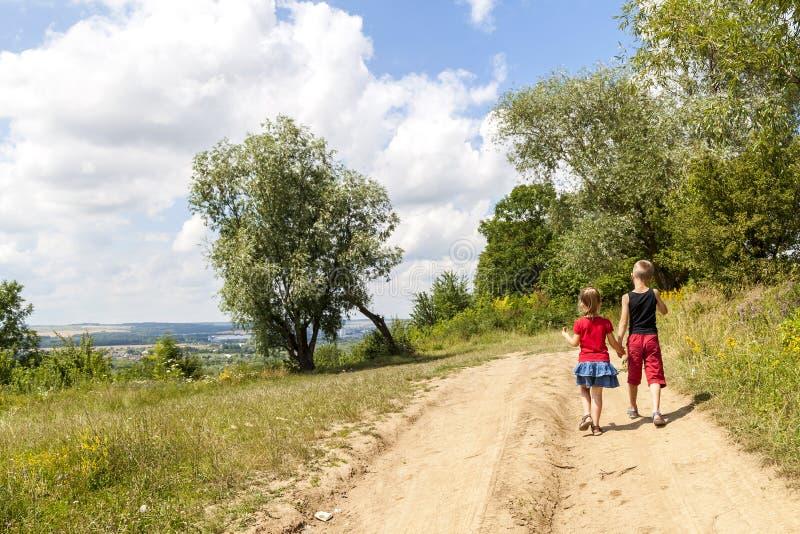 Ein Junge und Kinder eines Mädchens gehen auf einen Schotterweg an einem sonnigen Sommertag Scherzt Händchenhalten zusammen beim  lizenzfreies stockfoto