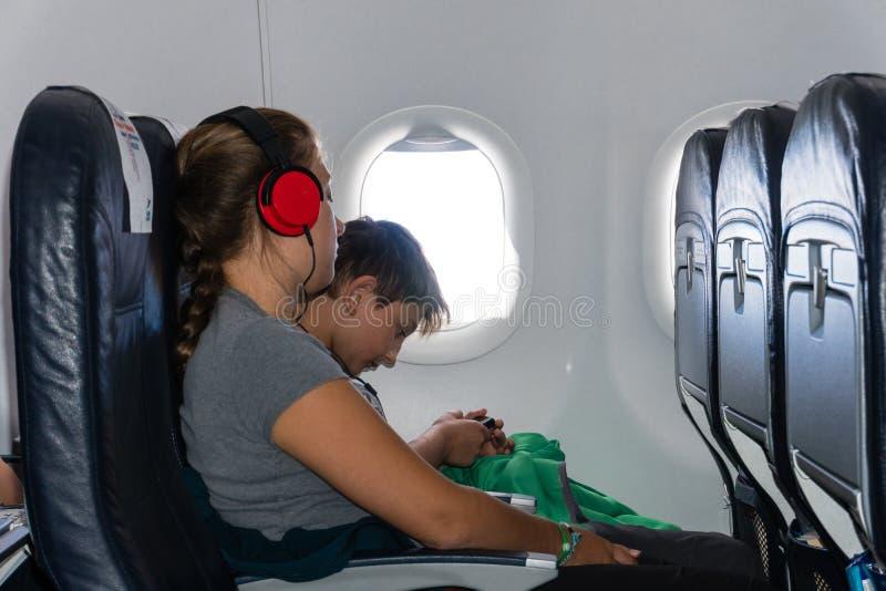 Ein Junge und ein Mädchen hören Musik, die im Flugzeug sitzt stockfoto