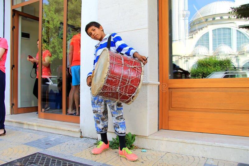 Ein Junge verdient Geld Spielen der alten Trommel Die Moschee Abu-Bekr wird in einem Fenster reflektiert lizenzfreies stockbild