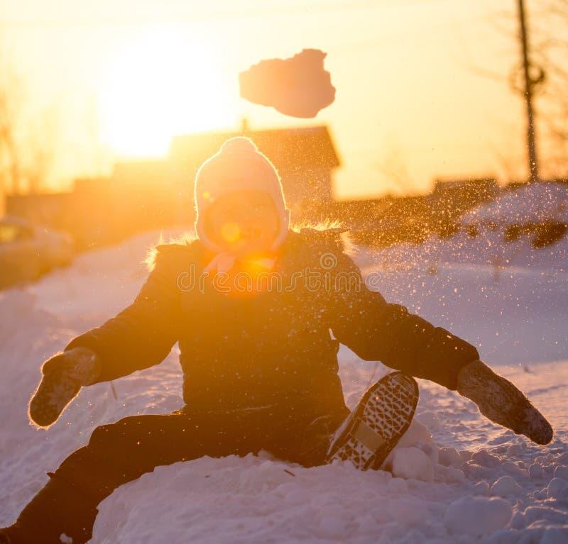 Ein Junge wirft Schnee in den Himmel bei Sonnenuntergang lizenzfreies stockfoto
