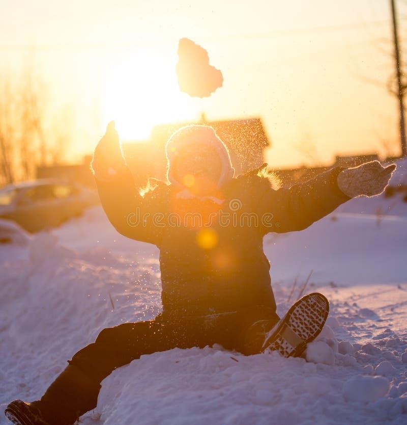 Ein Junge wirft Schnee in den Himmel bei Sonnenuntergang lizenzfreie stockfotografie