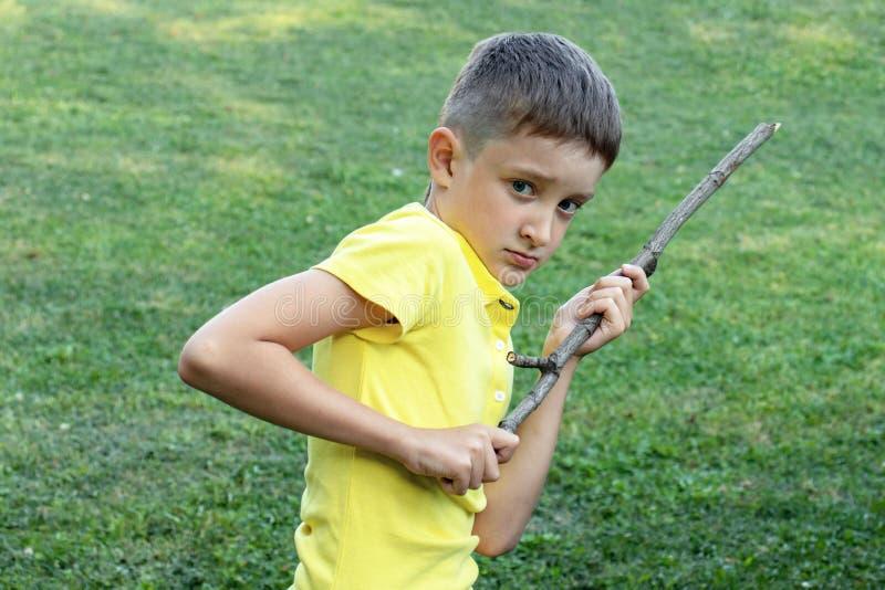 Ein Junge witn verärgertes Gesicht, das einen Stock in seinen Händen hält stockfotos