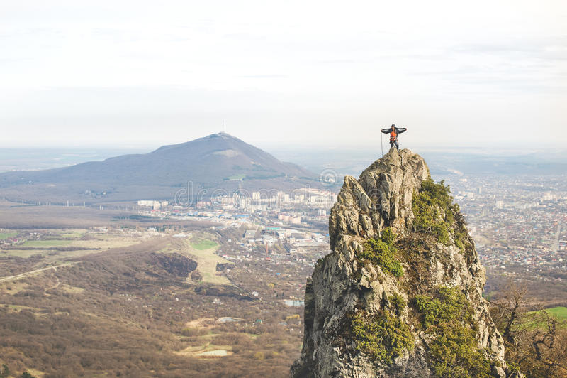Ein Jungebergsteiger wickelt das Seil zu den Oberteilen einer steilen Klippe gegen den Hintergrund der Stadt und des kaukasischen lizenzfreie stockfotografie