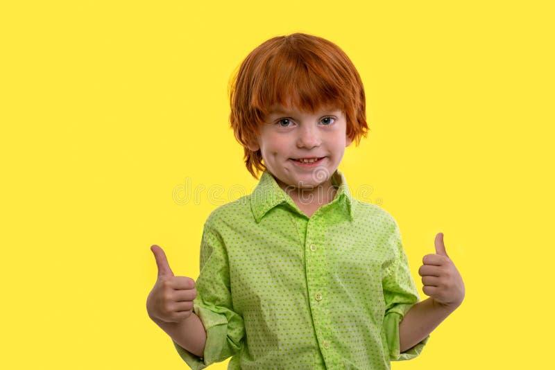 Ein Jungenrothaar, welches das grüne Hemd civing ist Sie eine anerkennend Geste, lokalisiert auf gelbem Hintergrund trägt stockfotos