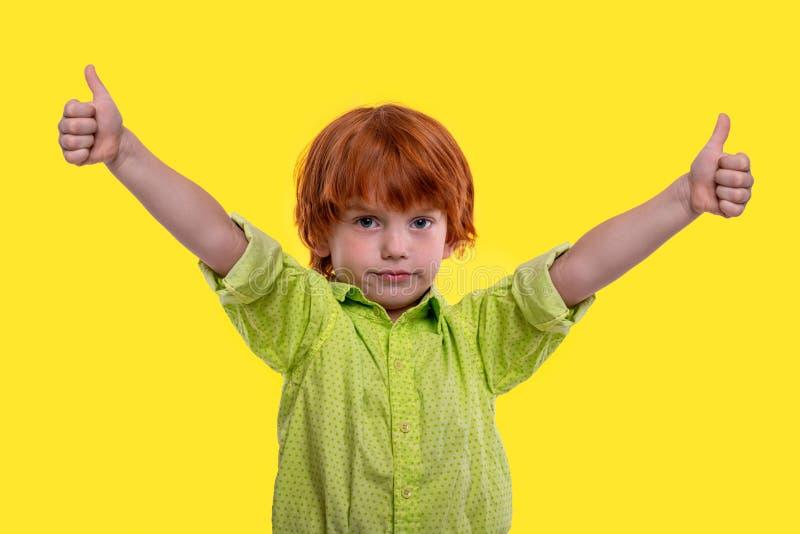 Ein Jungenrothaar, welches das grüne Hemd civing ist Sie eine anerkennend Geste, lokalisiert auf gelbem Hintergrund trägt lizenzfreie stockbilder