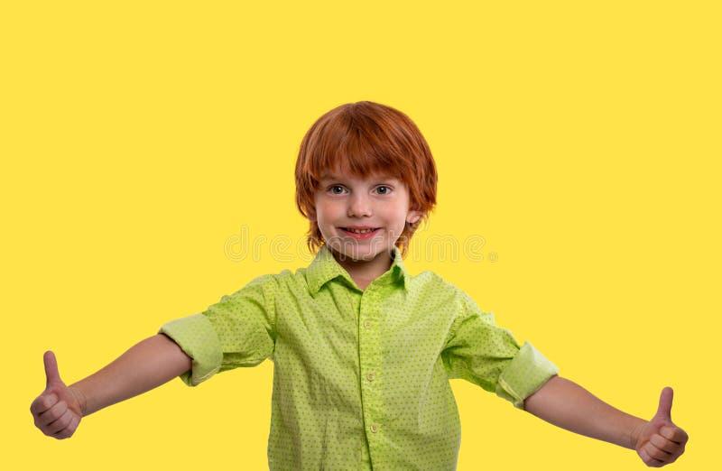 Ein Jungenrothaar, welches das grüne Hemd civing ist Sie eine anerkennend Geste, lokalisiert auf gelbem Hintergrund trägt lizenzfreies stockfoto