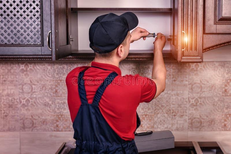 Ein junger Arbeitnehmer baut moderne hölzerne Küchenmöbel zusammen lizenzfreies stockbild