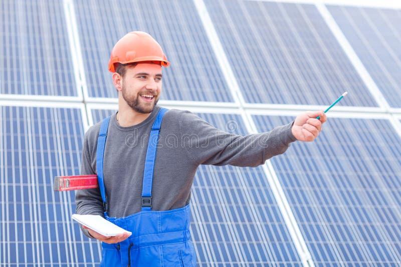 Ein junger Arbeitnehmer an der Solarbatteriestation in der Uniform zeigt seine Hand irgendwo und hält ein Notizbuch und waterpas stockbild