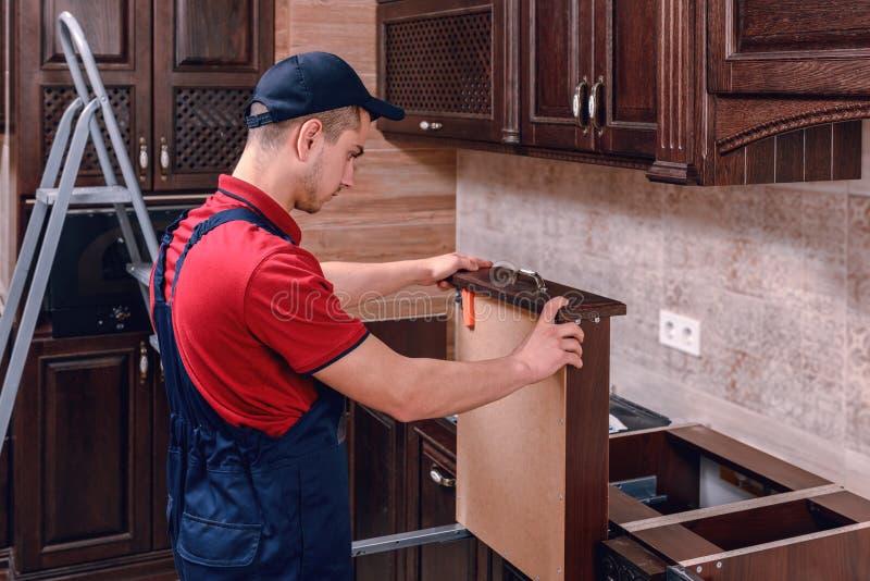 Ein junger Arbeitnehmer installiert ein Fach Installation von modernen hölzernen Küchenmöbeln lizenzfreies stockfoto