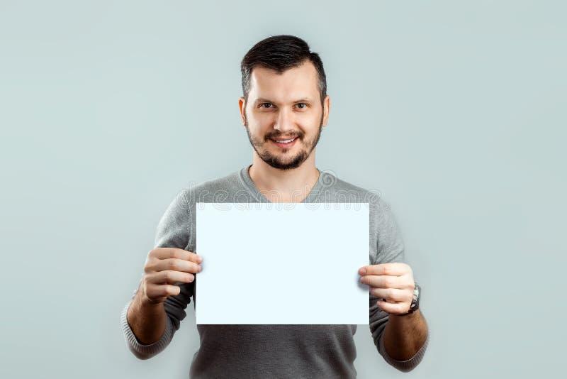 Ein junger, attraktiver Mann, der ein leeres weißes Blatt A4, auf einem hellen Hintergrund hält Modell, Plan, Kopienraum lizenzfreies stockbild