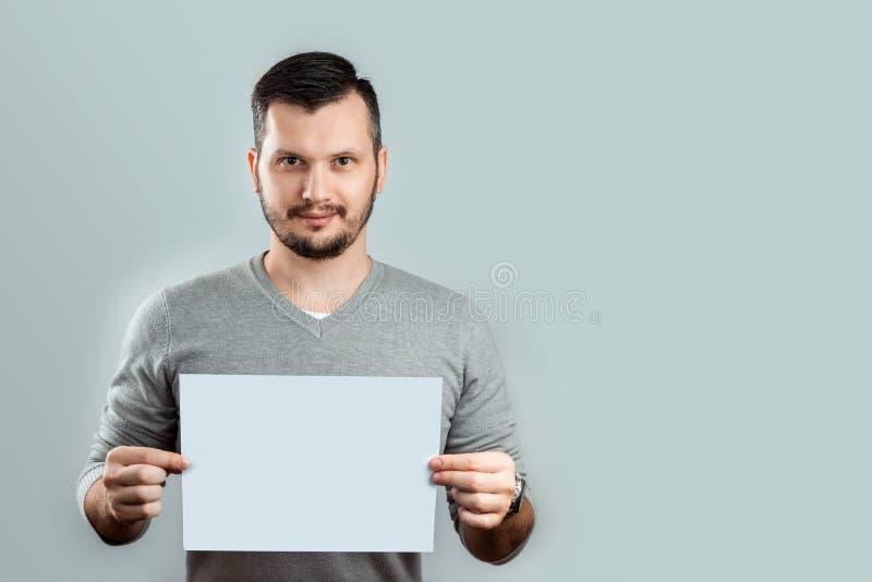 Ein junger, attraktiver Mann, der ein leeres wei?es Blatt A4, auf einem hellen Hintergrund h?lt Modell, Plan, Kopienraum lizenzfreie stockfotos