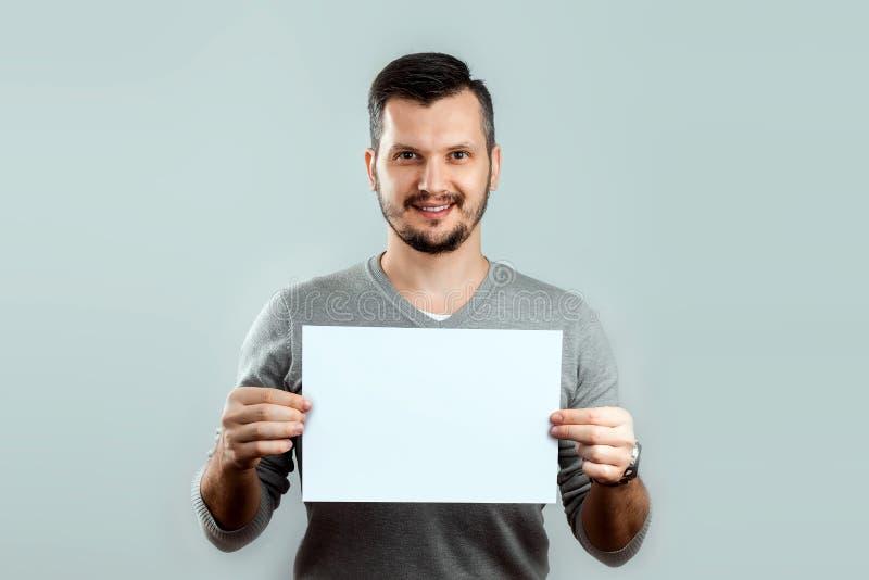 Ein junger, attraktiver Mann, der ein leeres wei?es Blatt A4, auf einem hellen Hintergrund h?lt Modell, Plan, Kopienraum stockbilder