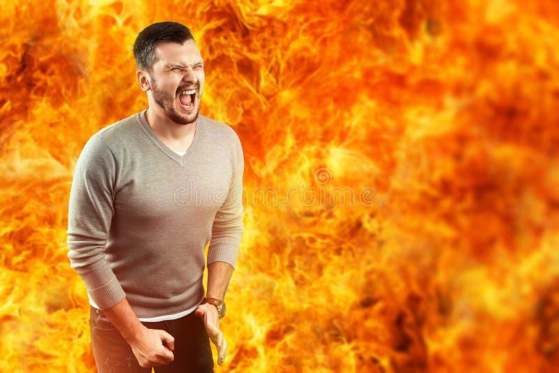 Ein junger attraktiver Mann glaubt den Schmerz in einer Flamme, umgeben durch heißes Feuer Er glaubt Hass, Ärger, Ärger, Neid stockbilder