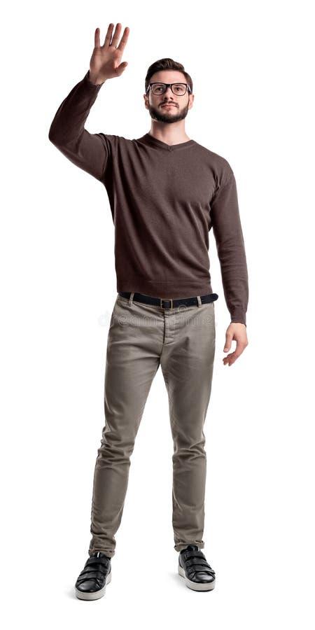 Ein junger bärtiger Mann in den Frachthosen halten seine Hand, um etwas zu berühren oder wellenartig zu bewegen lizenzfreies stockbild