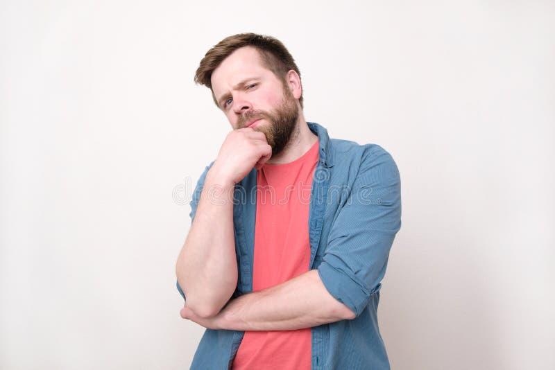 Ein junger b?rtiger skeptischer Mann untersucht die Kamera Ein Ausdruck des Misstrauens und des Misstrauens Getrennt auf wei?em H stockfotos