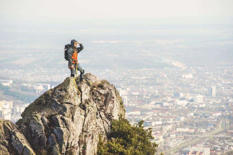 Ein junger Bergsteiger, der aus der Spitze einer steilen Klippe heraus vor dem hintergrund der kaukasischen Stadt und der Berge s lizenzfreies stockfoto