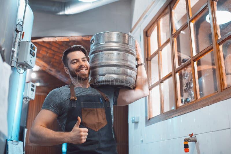 Ein junger Brauer in einem Schutzblech h?lt ein Fass mit Bier in den H?nden einer Brauerei lizenzfreie stockfotos
