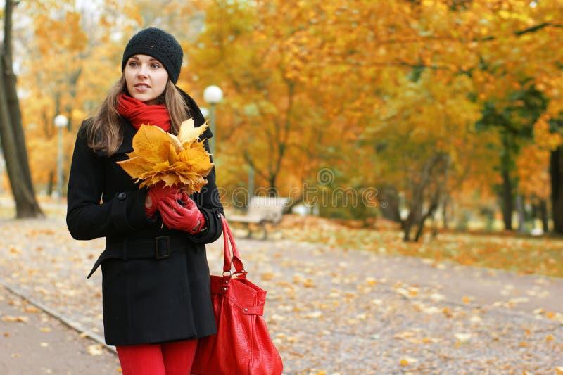 Ein junger Brunette in der warmen Kleidung in einem Park lizenzfreies stockbild