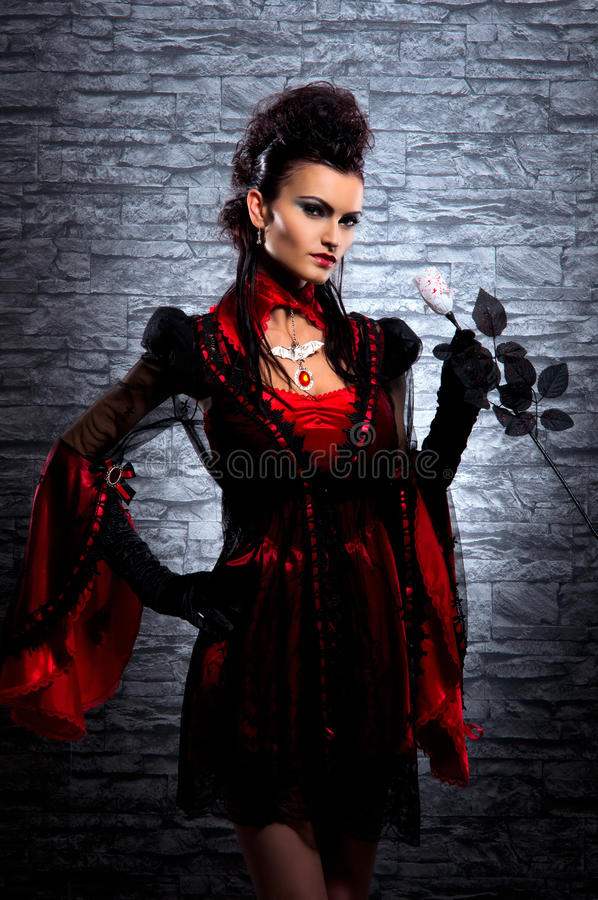 Ein junger Brunettedame-Vampir, der eine Rose anhält stockfoto