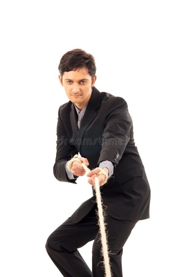 Ein junger Brunettegeschäftsmann, der das Seil zieht lizenzfreie stockfotos