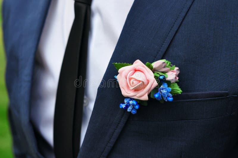 Ein junger dünner Mann in einem klassischen Anzug mit einer Bindung und ein weißes Hemd und eine Rose in seinem Knopfloch stockfotos