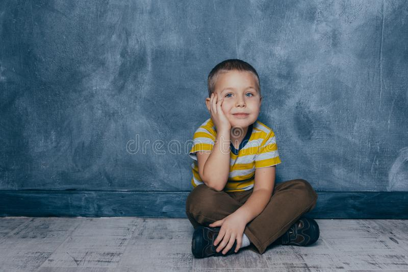 Ein junger emotionaler Junge sitzt auf einem Bretterboden vor dem hintergrund einer blauen Wand im Studio Menschliche Gef?hle stockfotografie