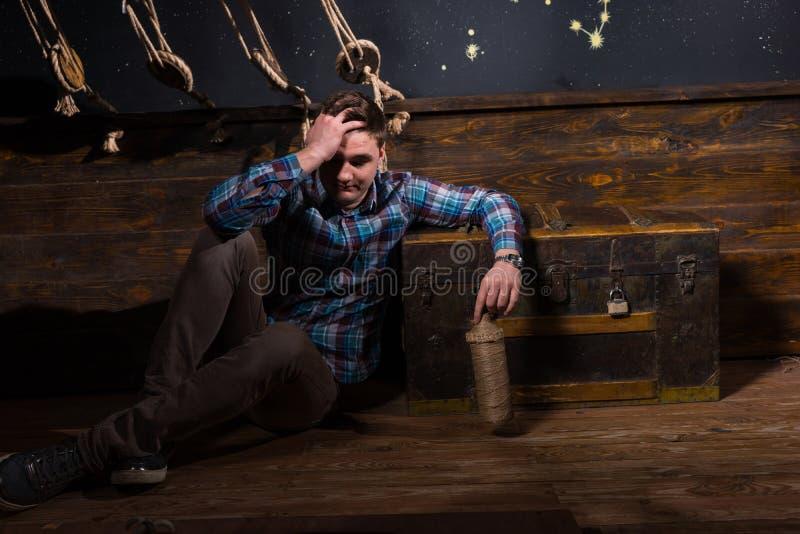 Ein junger enttäuschter Mann sitzt nahe einem Kasten und hält Glasflasche lizenzfreies stockfoto