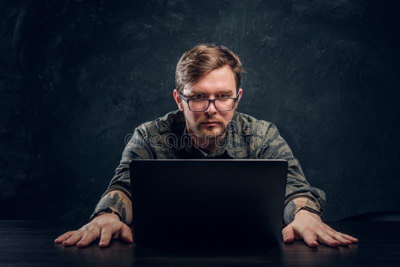 Ein junger erfahrener Programmierer in einer stilvollen Militärhemdfunktion auf einem Laptop in einem dunklen Büro lizenzfreie stockfotos