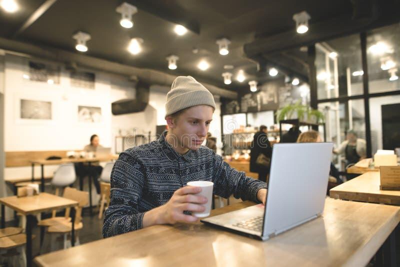 Ein junger Freiberufler arbeitet für einen Laptop in einem gemütlichen Café für einen Tasse Kaffee Der Student benutzt das Intern stockbild