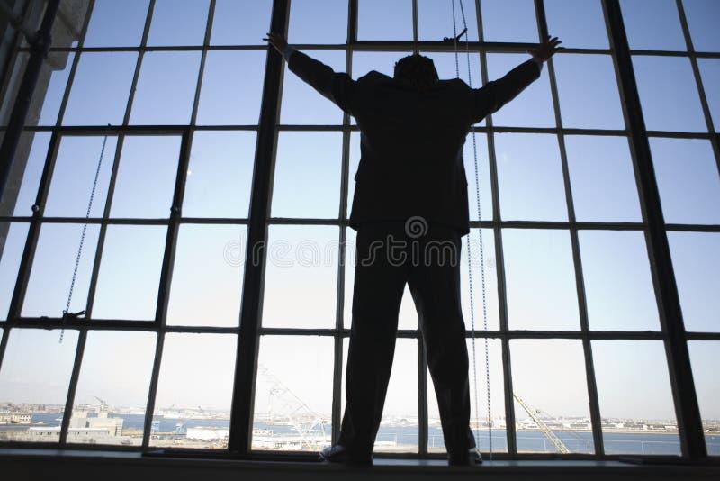 Ein junger Geschäftsmann, der an steht und heraus ta schaut lizenzfreies stockbild