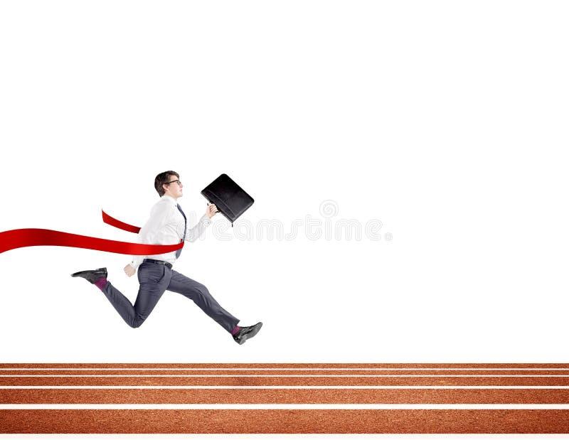 Ein junger Geschäftsmann, der vorwärts auf Bahn mit einem schwarzen Ordner in der Hand kreuzt die rote Ziellinie läuft lizenzfreie stockfotografie