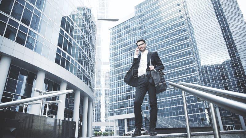 Ein junger Geschäftsmann spricht am Telefon auf der Treppe lizenzfreie stockfotografie