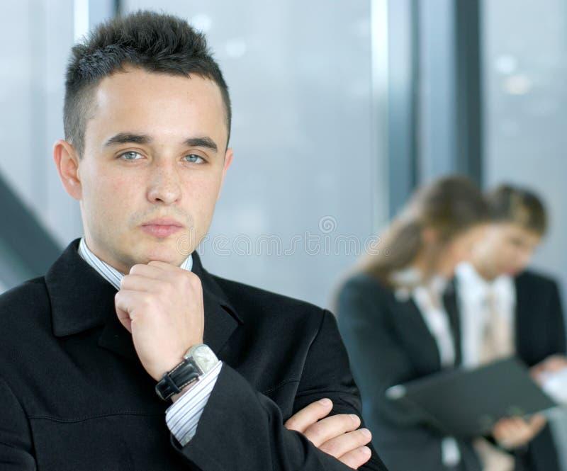 Ein junger Geschäftsmann vor seinen Kollegen stockfotografie