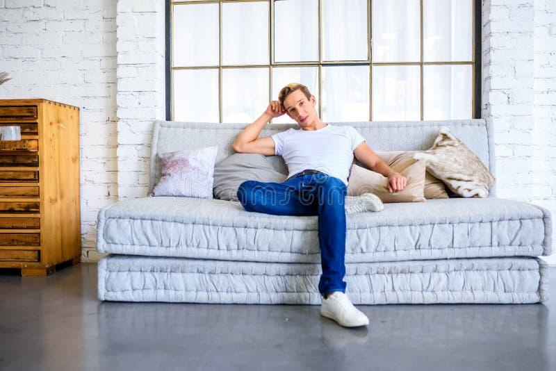 Ein junger gutaussehender Mann, der auf dem Sofa in einem Dachbodenart apartm sich entspannt stockfotografie
