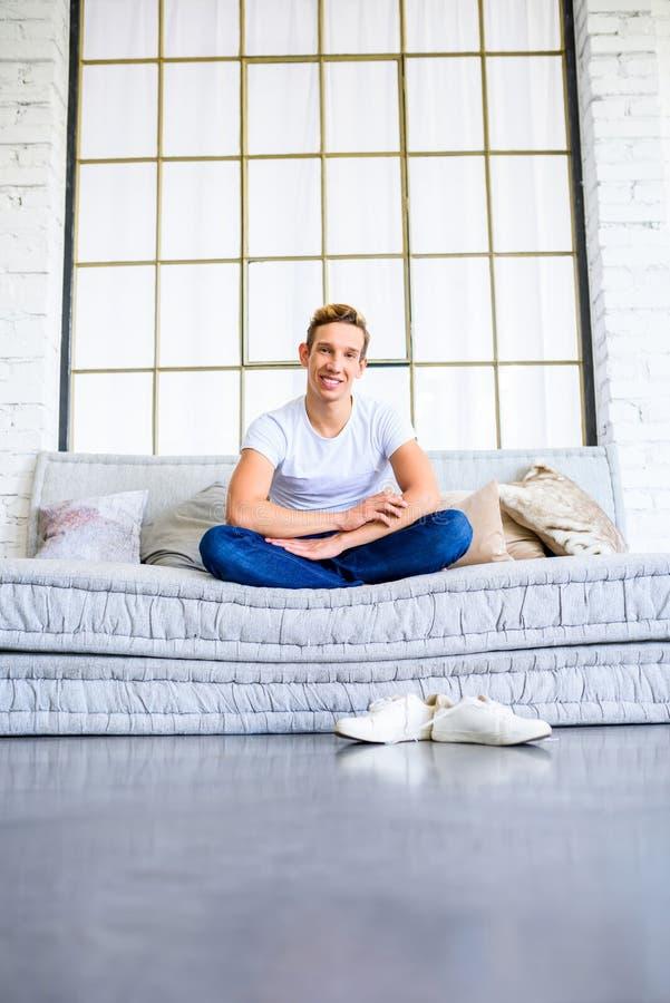 Ein junger gutaussehender Mann, der auf dem Sofa in einem Dachbodenart apartm sich entspannt stockbilder