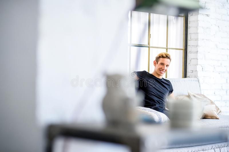 Ein junger gutaussehender Mann, der auf dem Sofa in einem Dachbodenart apartm sich entspannt lizenzfreie stockfotos