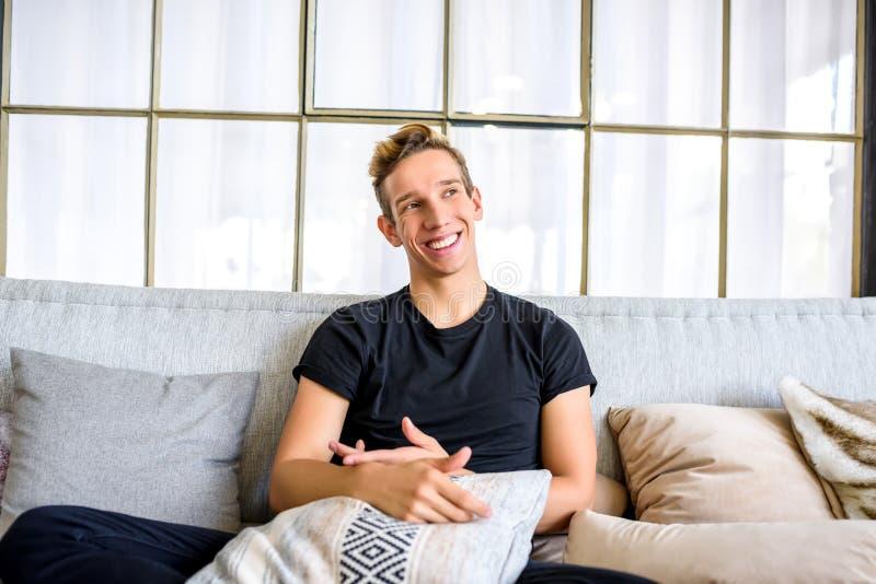 Ein junger gutaussehender Mann, der auf dem Sofa in einem Dachbodenart apartm sich entspannt stockfotos