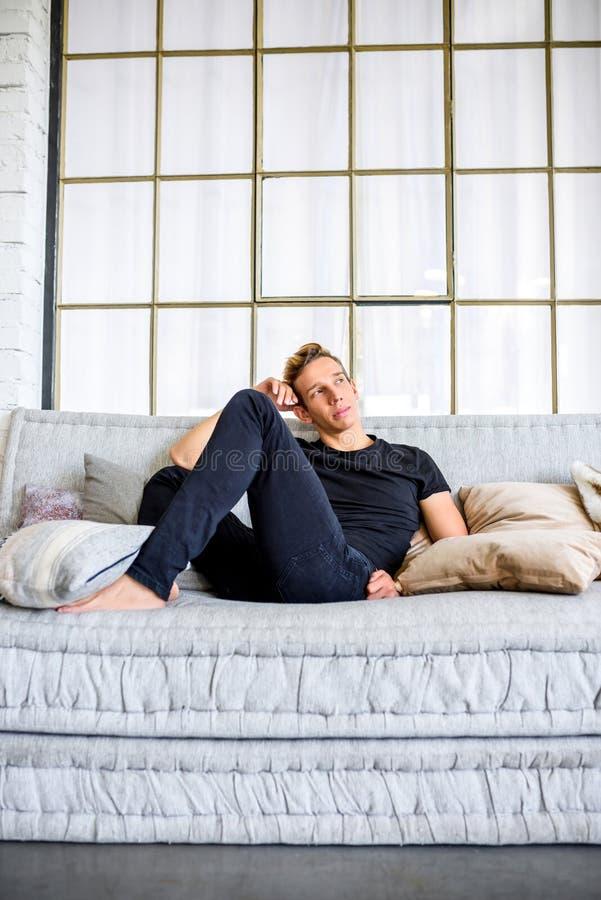 Ein junger gutaussehender Mann, der auf dem Sofa in einem Dachbodenart apartm sich entspannt stockbild